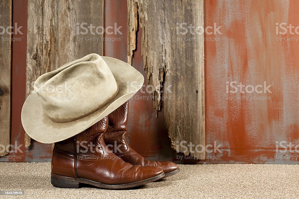 Cowboy boots and hat rustic background royalty-free stock photo