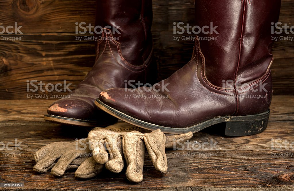 Cowboy boots and leather gloves. stock photo