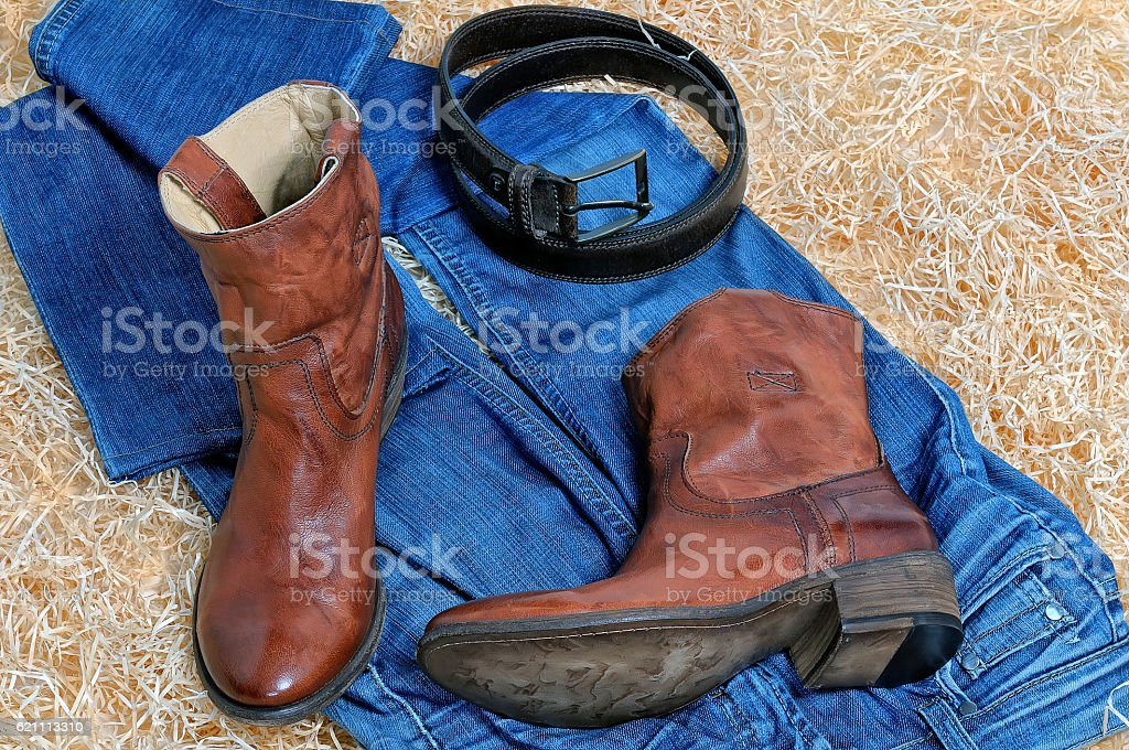 Cowboy boots leather belt and blue jeans on straw stock photo