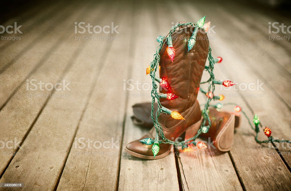 Cowboy Boots with Christmas Lights on Old Wood Background stock photo