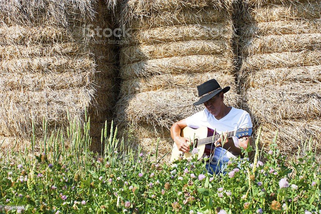 Cowboy by haystack plays guitar horizontal royalty-free stock photo