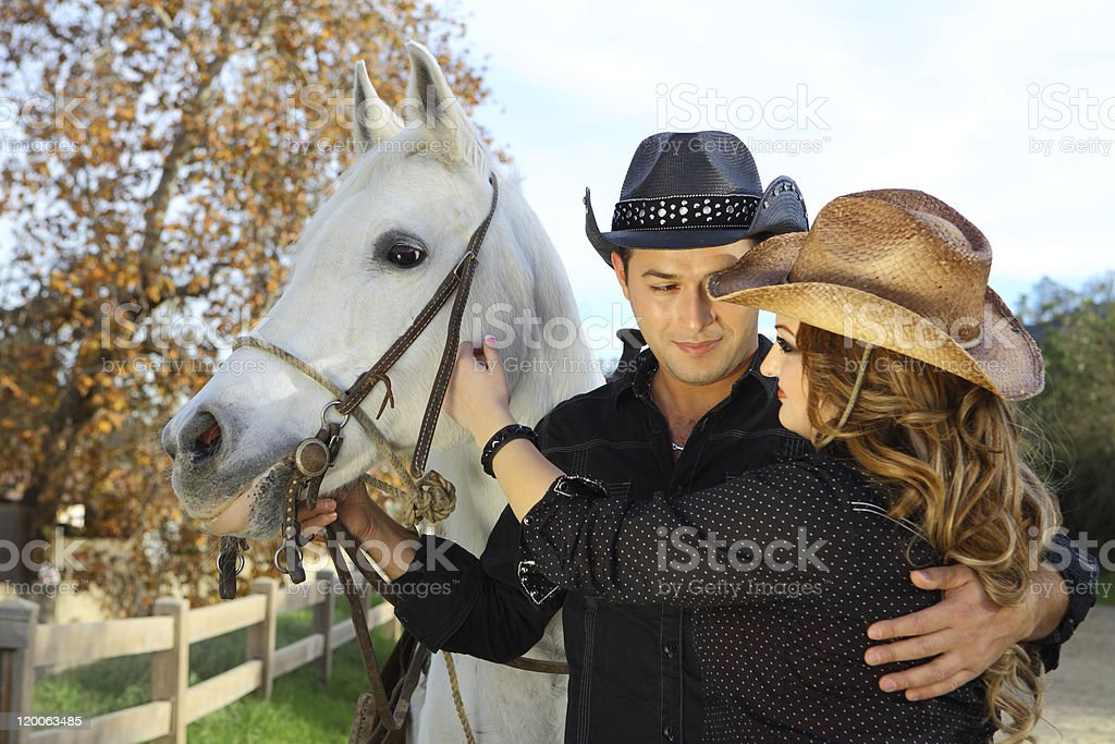 Cowboy Couple In Love With A White Horse royalty-free stock photo