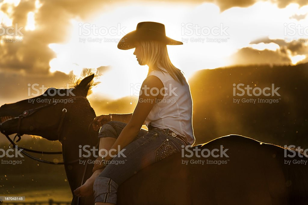 Cowboy: Cowgirl resting on horse. Beautiful sunset royalty-free stock photo