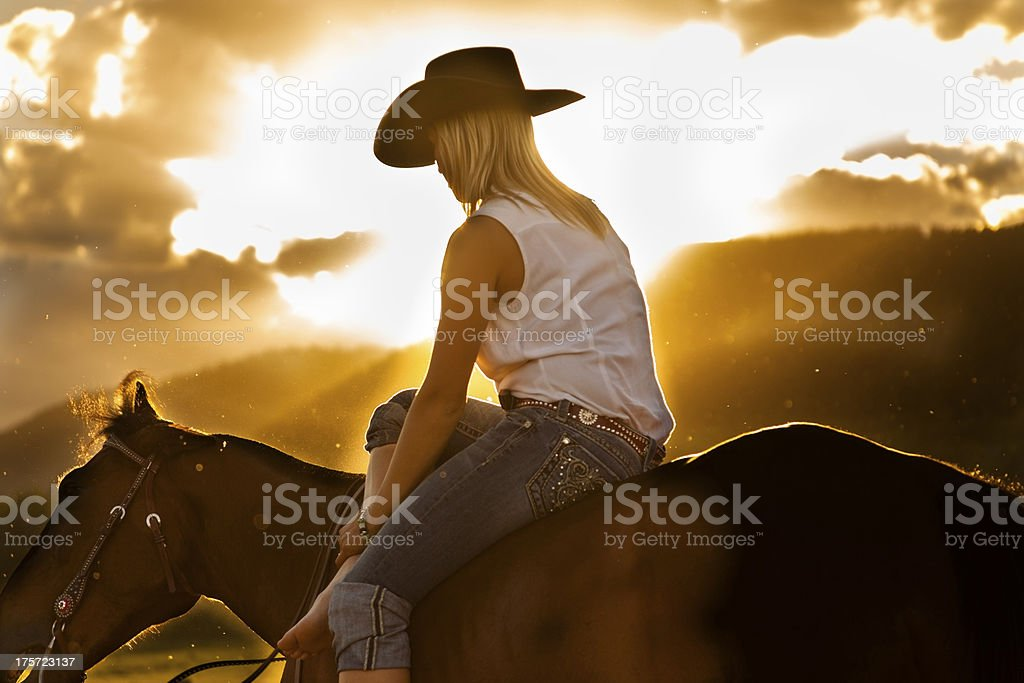Cowboy: Cowgirl taking a break on horse. Beautiful sunset. stock photo