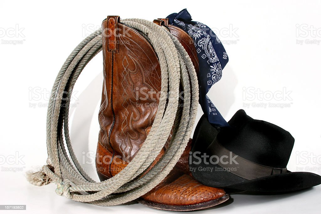 Cowboy gear: boots, hat, rope and bandana. Isolated on white. stock photo