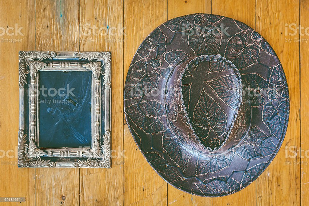 Cowboy hat and empty picture frame on wooden background stock photo