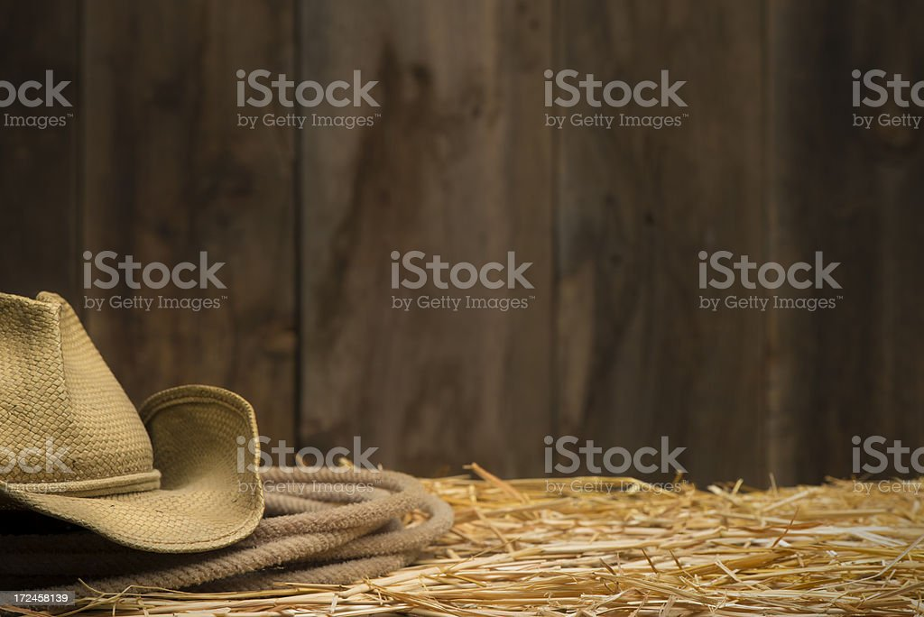 Cowboy hat and rope on straw-barnwood wall with copy space stock photo