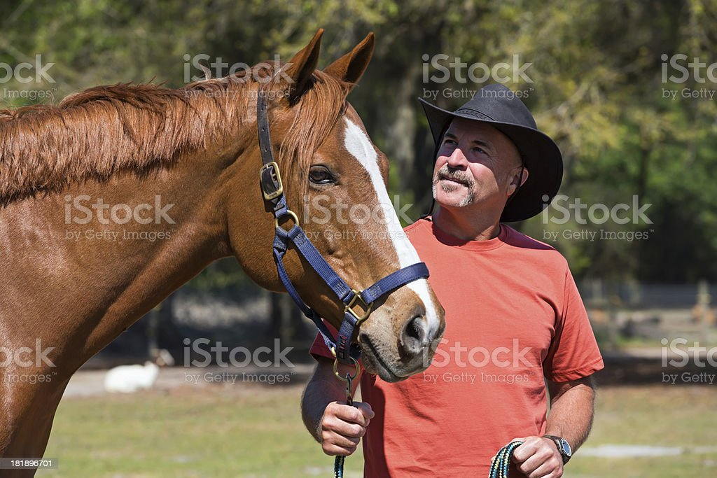 cowboy holding his horse royalty-free stock photo