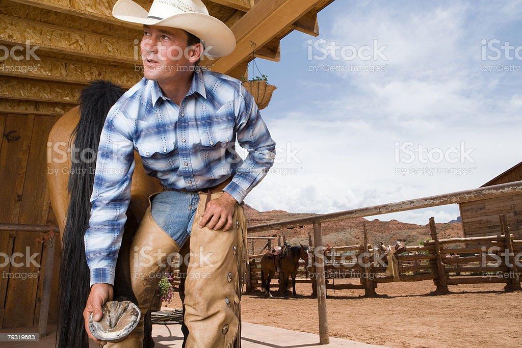 Cowboy holding horse hoof royalty-free stock photo