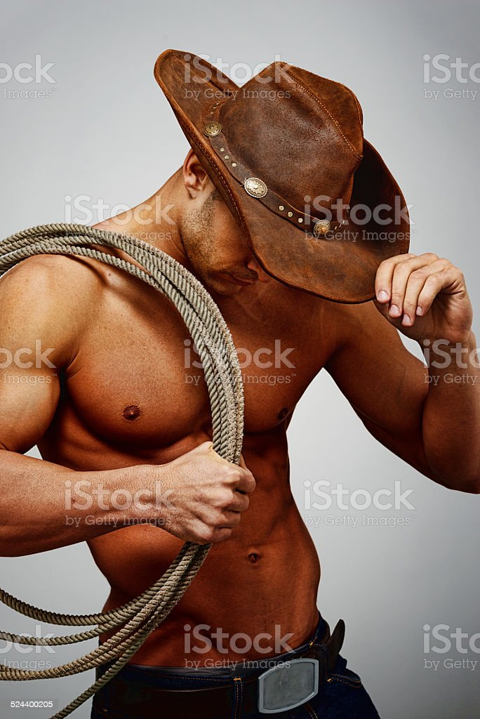 Cowboy holding lasso on his shoulder looking down stock photo