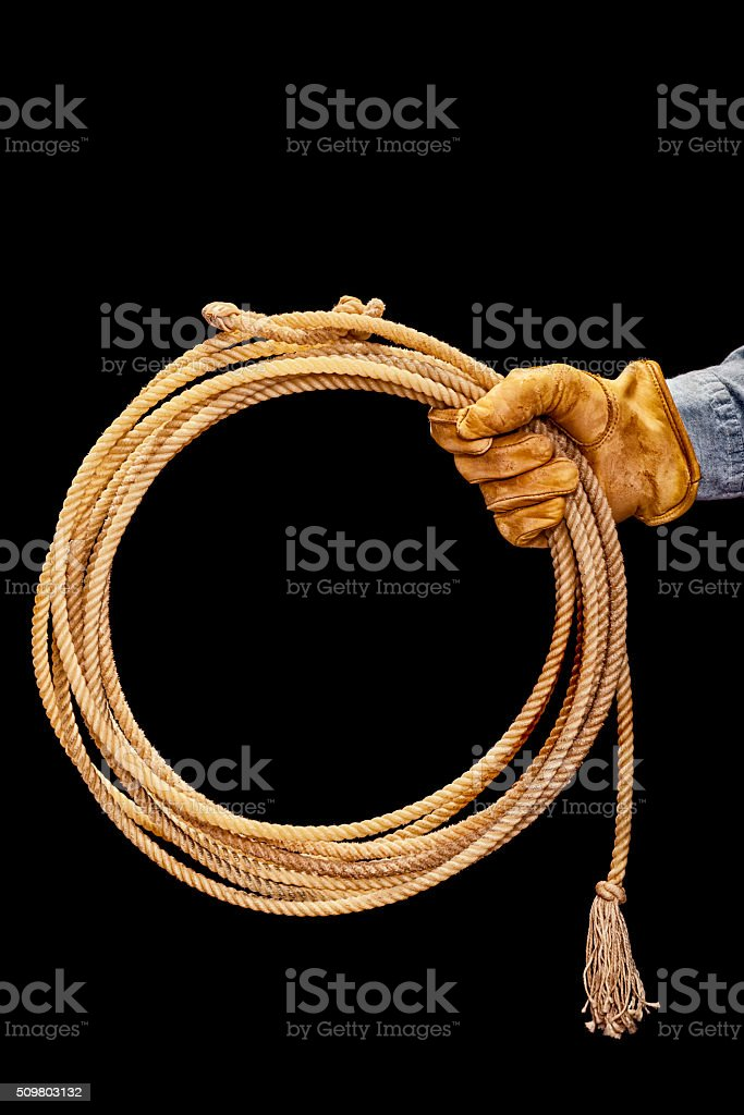 Cowboy holding out lasso against a black background stock photo