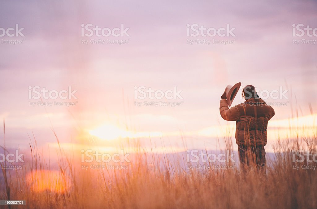 Cowboy holds hat while standing in hay looking at sunset stock photo
