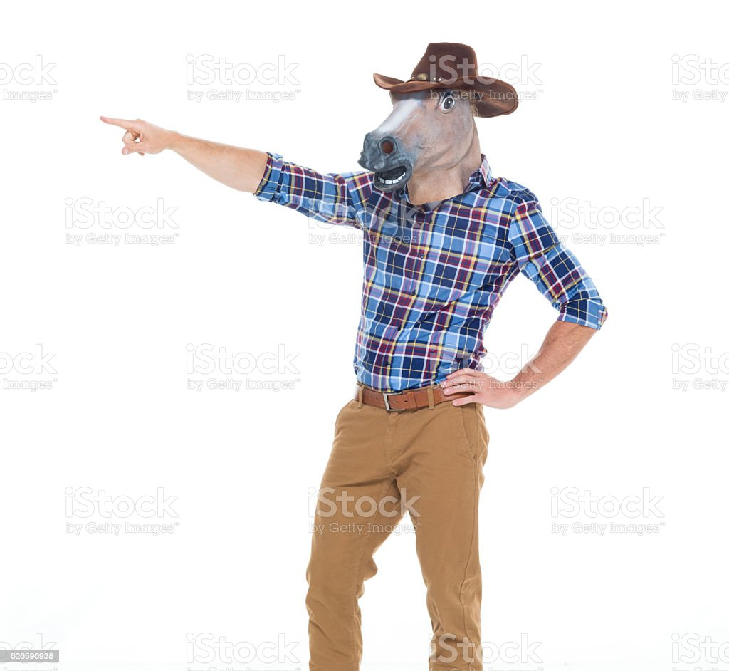 Cowboy in horse costume and pointing away stock photo