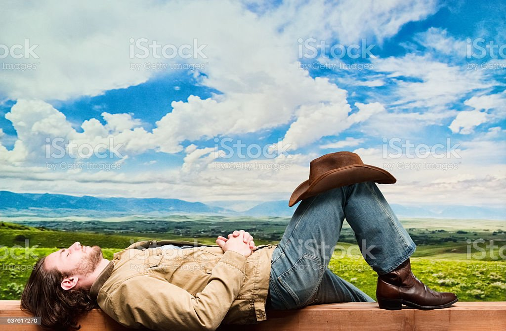 Cowboy lying on bench outdoors stock photo