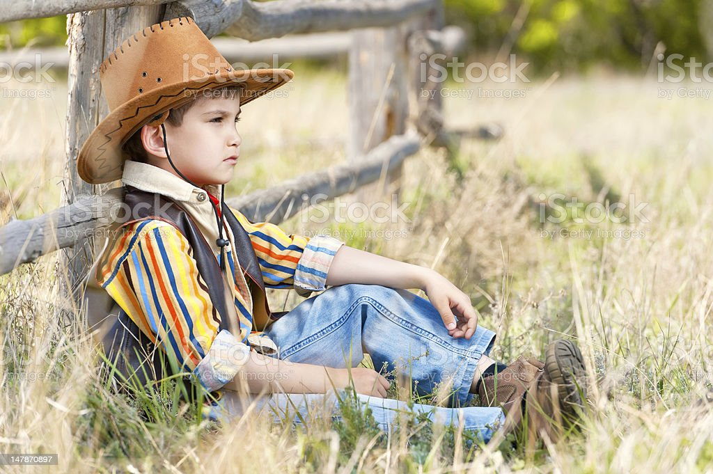 Cowboy on a grass at old fence royalty-free stock photo