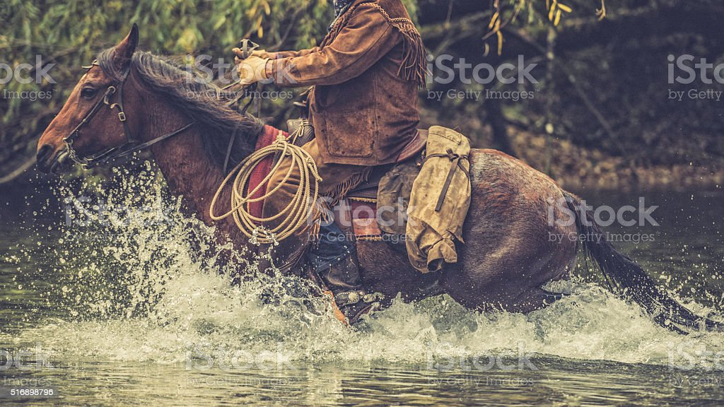 Cowboy on a horse riding across a river stock photo