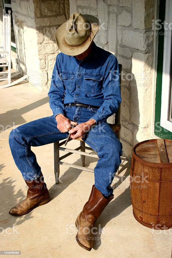 Cowboy on porch whittling  a stick. royalty-free stock photo