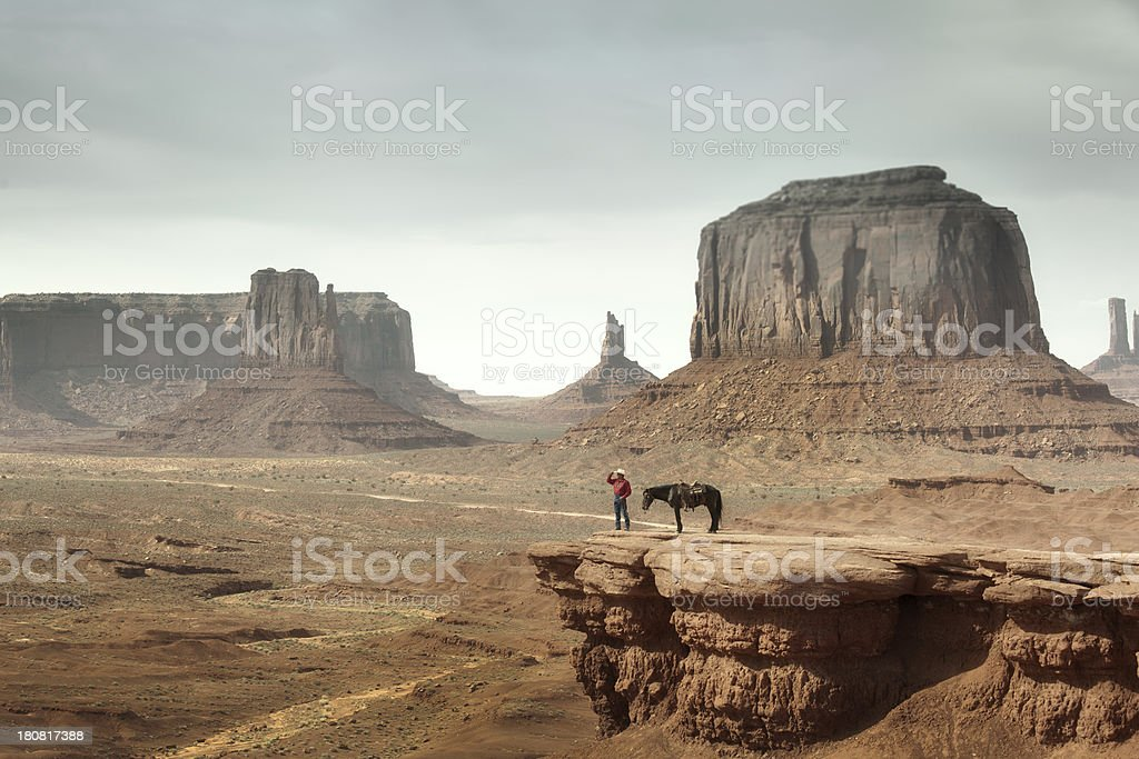 Cowboy on the Cliff of Monument Valley in American Southwest royalty-free stock photo