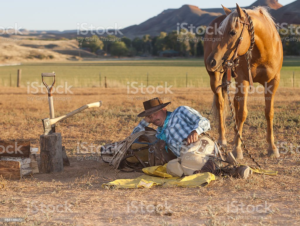 Cowboy rests on saddle with horse at his side stock photo