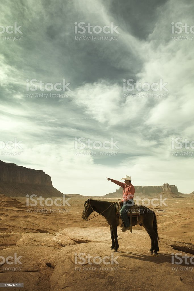 Cowboy Riding a Horse Pointing Direction in the American Southwest stock photo