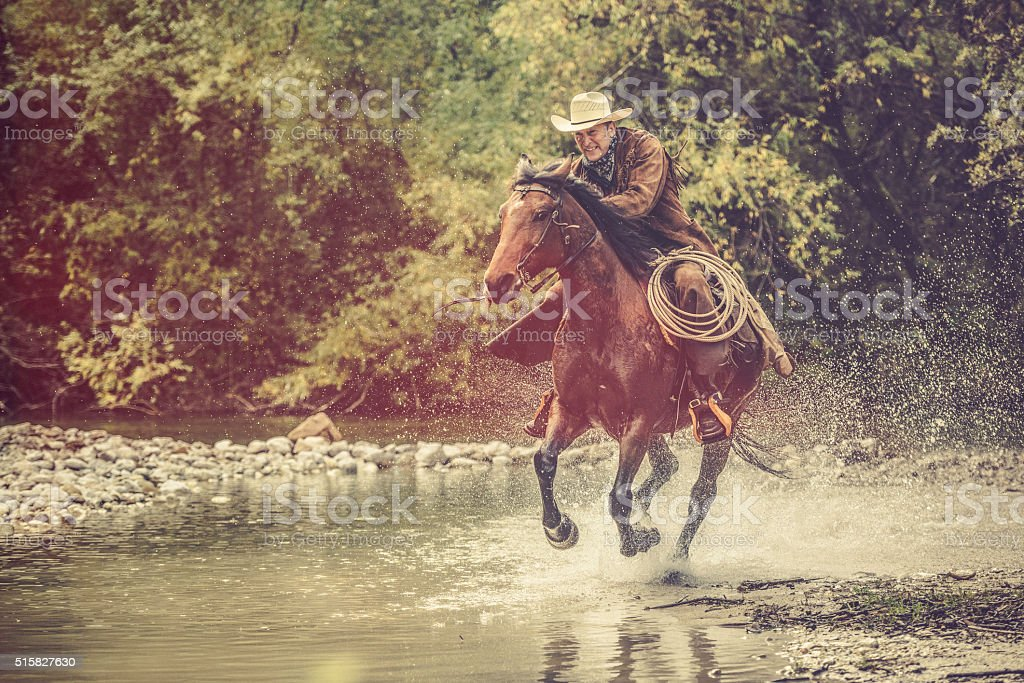Cowboy riding across a river in the forest stock photo