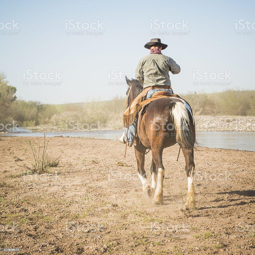 Cowboy riding away near River stock photo