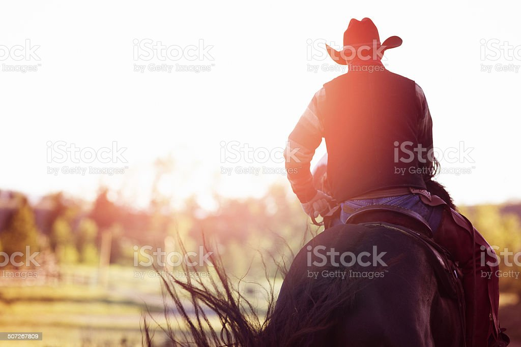 Cowboy riding away rear view stock photo