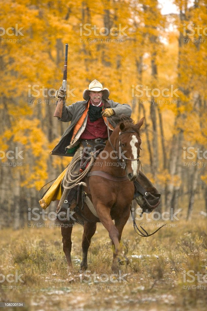 Cowboy riding in fall stock photo