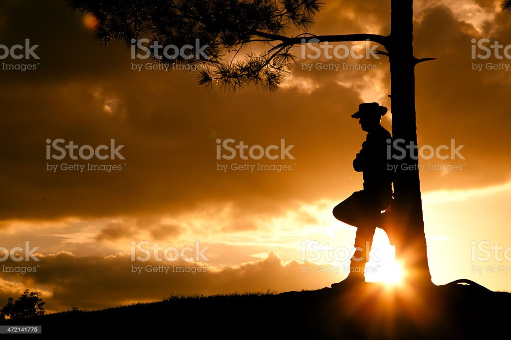 Cowboy: Silhouette rancher, farmer overlooks field after rainstorm at sunset. stock photo