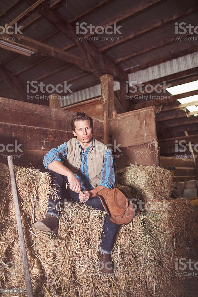Cowboy Sitting in the Barn on Top of Hay Stack stock photo