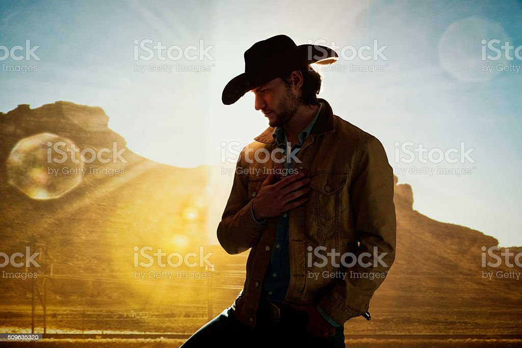 Cowboy standing in front of hill stock photo