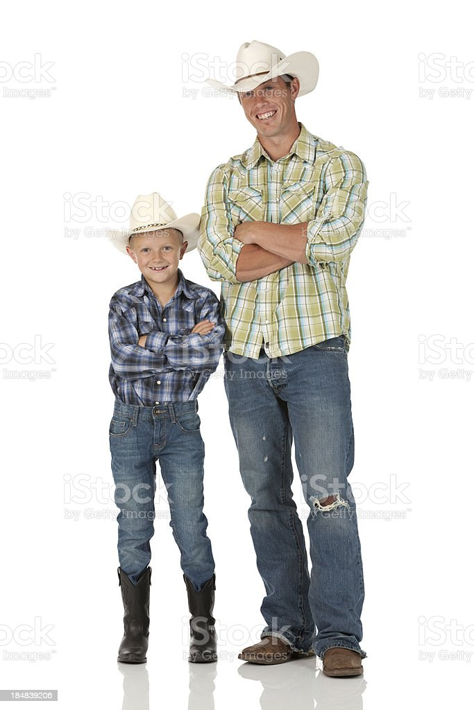 Cowboy standing with his son royalty-free stock photo
