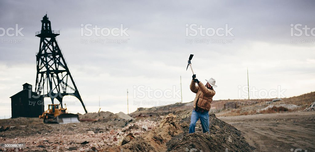 Cowboy swings pickaxe by old oil drill on western plain stock photo