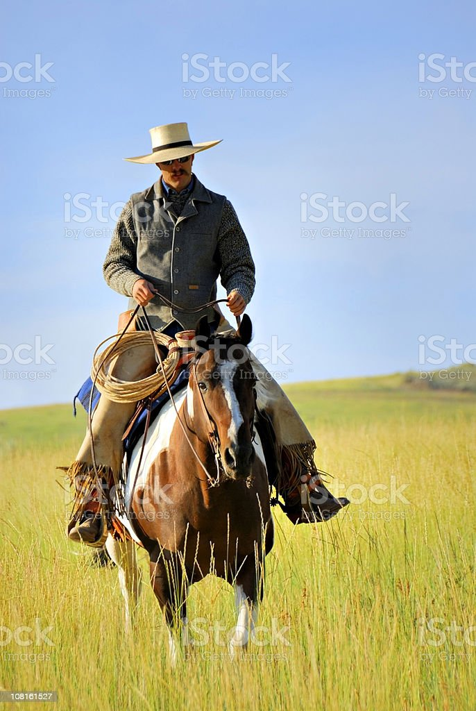 Cowboy Taking An Early Morning Ride On His Horse stock photo