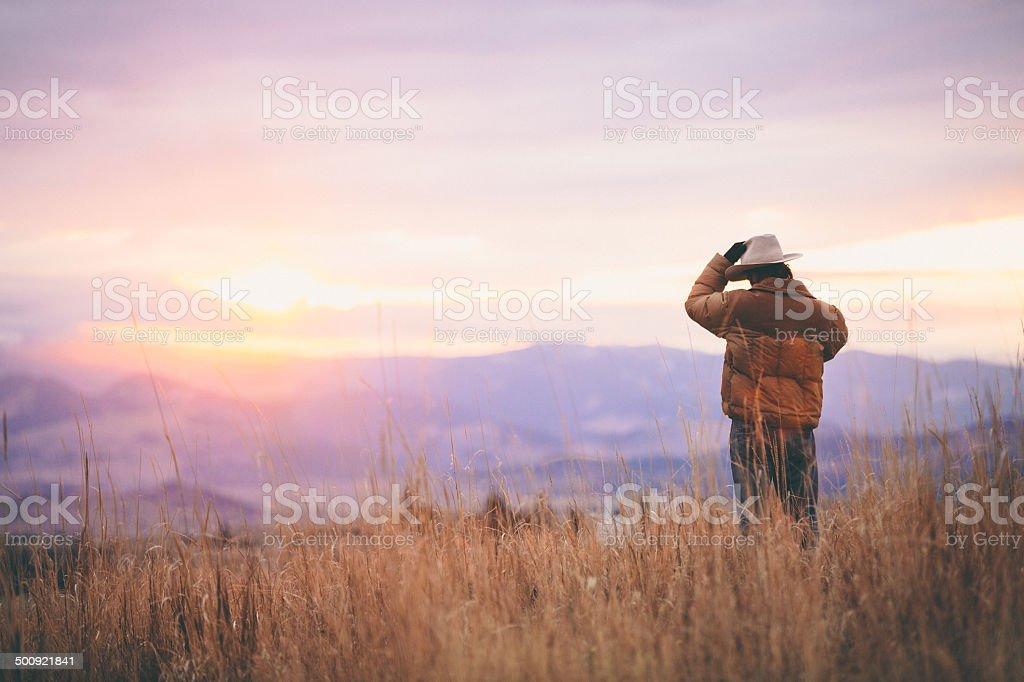Cowboy talks on phone while watching sunset over mountains stock photo