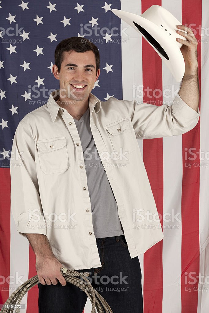 Cowboy tipping hat in front of an American flag stock photo
