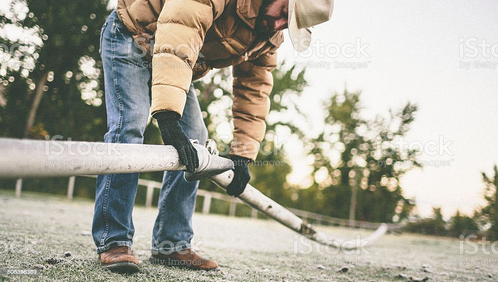 Cowboy wearing gloves works with irrigation pipe on farm stock photo