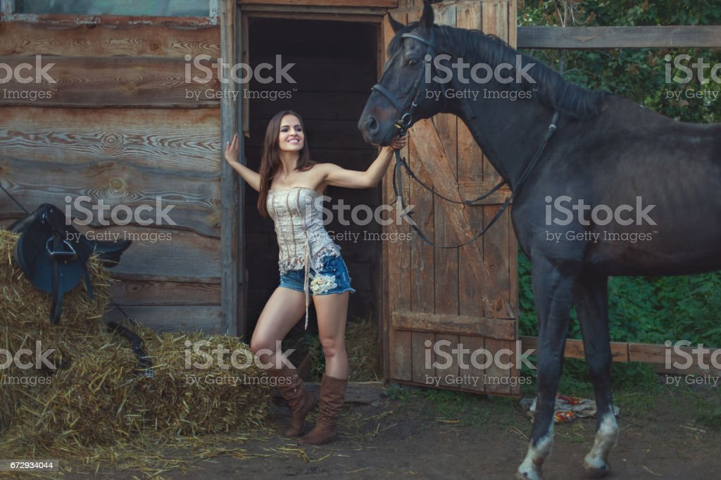 Cowboy woman is holding a horse. stock photo