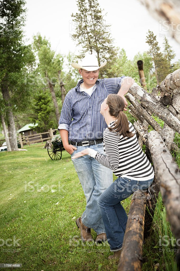 Cowboy: Wrangler talks to young woman on ranch grounds. royalty-free stock photo