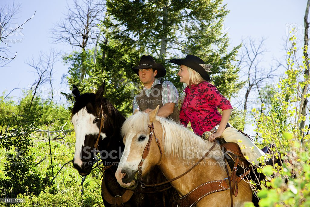 Cowboys: Couple on horse trail together. Recreational horseback riding. royalty-free stock photo