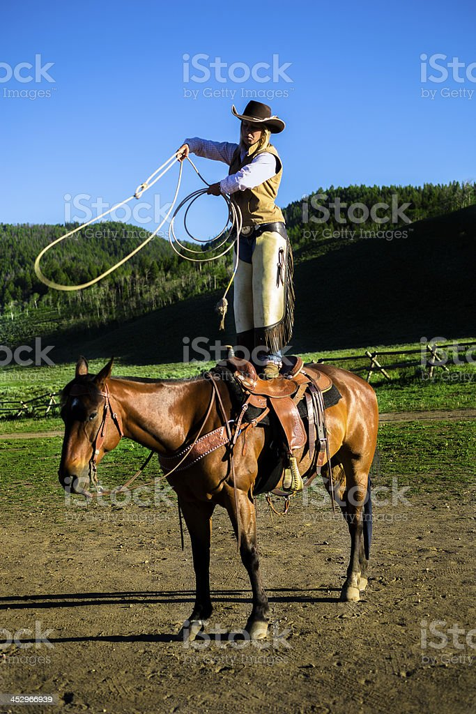Cowboys: Cowgirl standing on horse saddle swinging lasso. Ranch trick. royalty-free stock photo