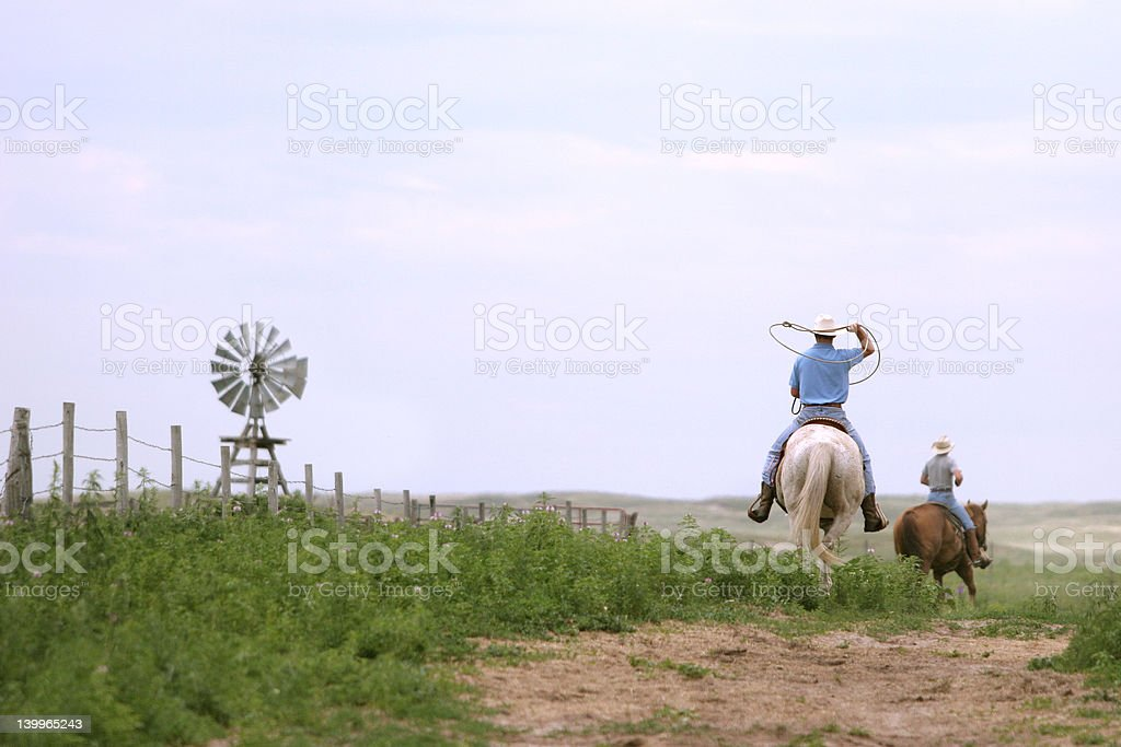 Cowboys lasso and ride the ranch stock photo