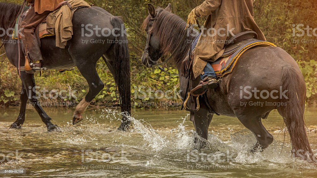 Cowboys on a horse riding across a river stock photo