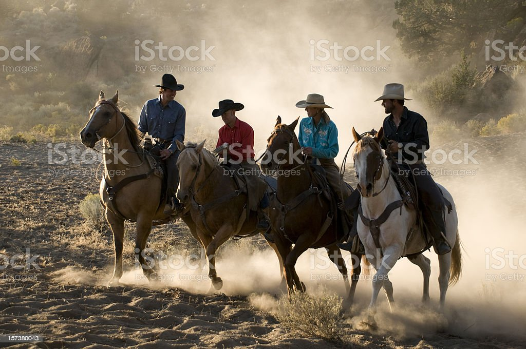 Cowboys on horses galloping through the sand stock photo