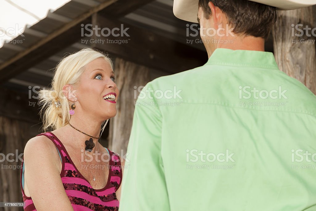 Cowboys: Texas cowboy talks with his cowgirl at ranch setting. stock photo