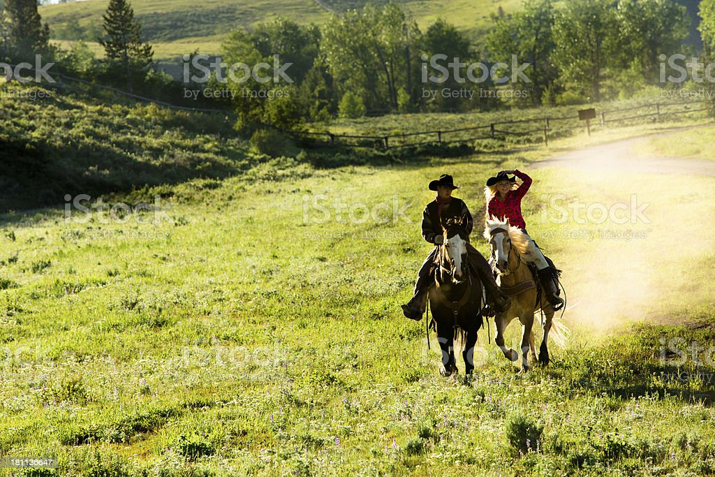 Cowboys: Wranglers ride horses through pasture. royalty-free stock photo