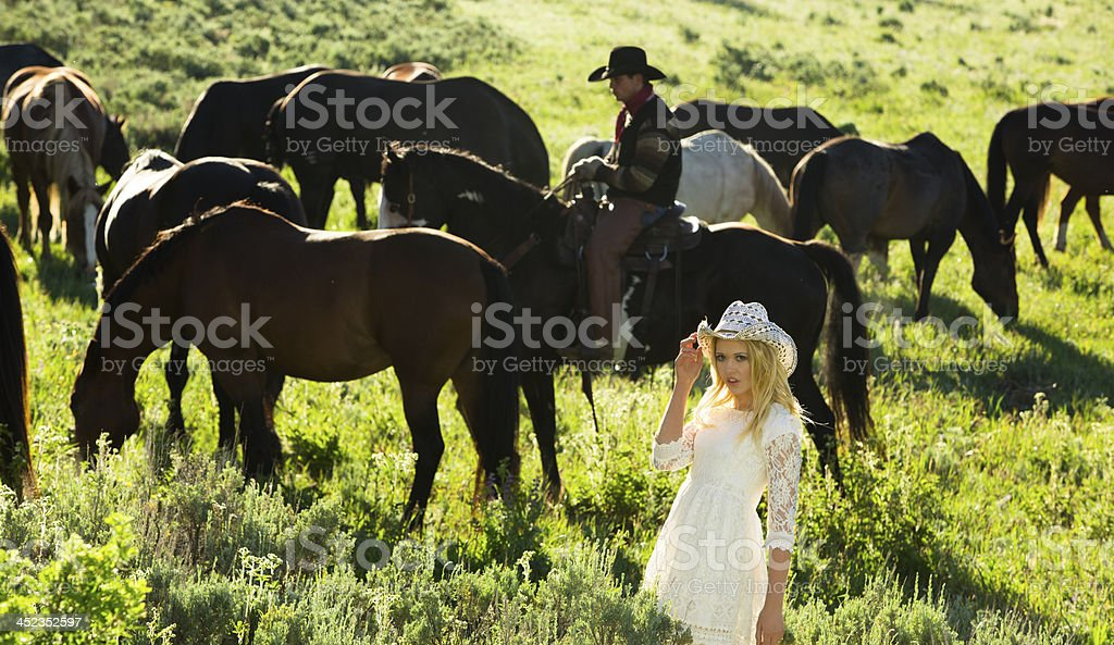 Cowboys: Young woman in pasture. Horse herd is grazing. Western. royalty-free stock photo