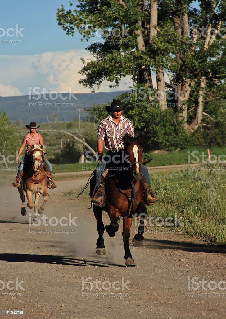 Cowgirl and Cowboy race each other on horses. stock photo
