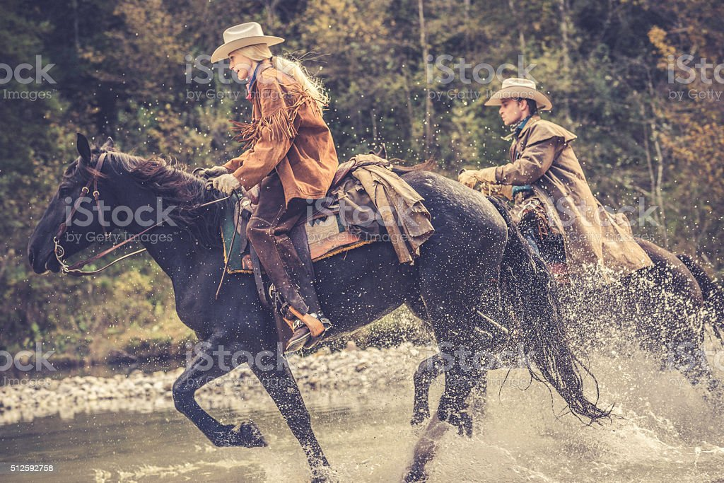 Cowgirl and cowboy riding across a river in the forest stock photo