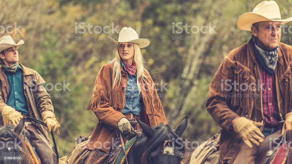Cowgirl and cowboys riding horses stock photo